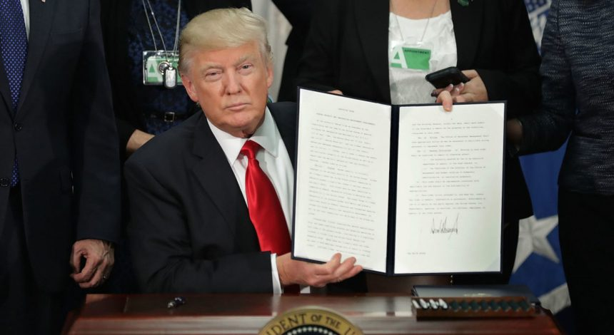 Picture of Donald Trump in Oval Office Holding up immigration Executive Orders