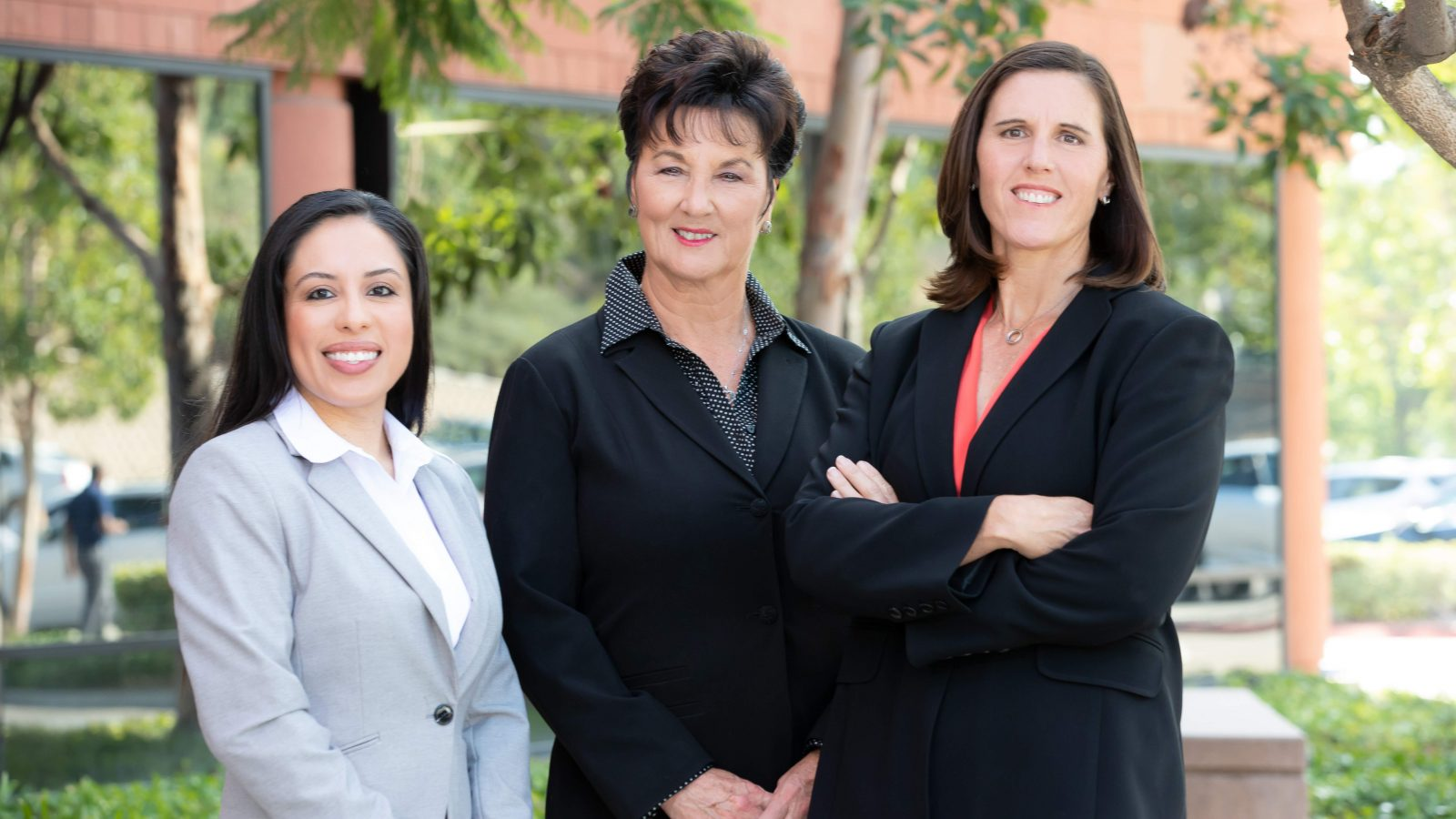 Three female lawyers in front of a building.