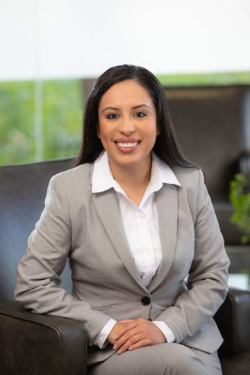 A hispanic lawyer wearing a gray suit, sitting in a chair with her hands folded.
